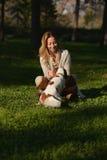 Den härliga flickan sitter i parkera och spelar med hennes stolta konung Charles Spaniel för hunden Royaltyfria Foton