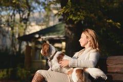 Den härliga flickan sitter på bänken i parkera och tycker om med hennes stolta konung Charles Spaniel för hunden Arkivfoton