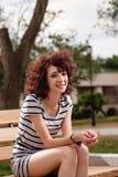 Den härliga flickan sitter på en parkerabänk på en bakgrund av G Royaltyfri Bild