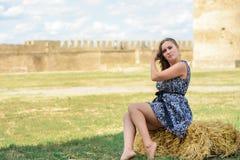 Den härliga flickan sitter på ett sugrör mot en bakgrund av en fästning royaltyfri fotografi