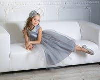 Den härliga flickan sitter på soffan Arkivfoto