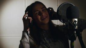 den härliga flickan sjunger barn Ung sångare som sjunger in i en mikrofon Stående som är nära upp av sångaren Inspelningstudio Royaltyfri Fotografi