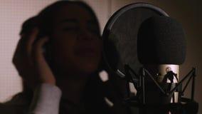den härliga flickan sjunger barn Ung sångare som sjunger in i en mikrofon Stående som är nära upp av sångaren Inspelningstudio Arkivfoto