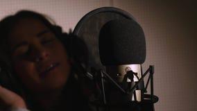 den härliga flickan sjunger barn Ung sångare som sjunger in i en mikrofon Stående som är nära upp av sångaren Inspelningstudio Royaltyfria Foton