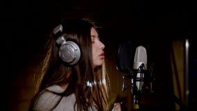 den härliga flickan sjunger barn Ung sångare som sjunger in i en mikrofon Stående som är nära upp av sångaren Inspelningstudio stock video
