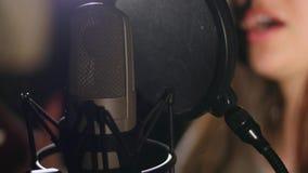 den härliga flickan sjunger barn Ung sångare som sjunger in i en mikrofon Stående som är nära upp av sångaren Arkivfoton
