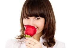 Den härliga flickan sniffar doften av rosen Royaltyfria Bilder