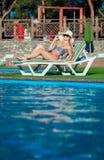Den härliga flickan solbadar i baddräkt med nöje Hon ligger nära en simbassäng Damen tycker om solen Royaltyfria Foton