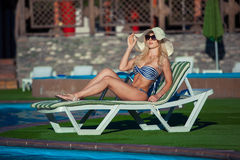 Den härliga flickan solbadar i baddräkt med nöje Hon ligger nära en simbassäng Damen tycker om solen Arkivbilder