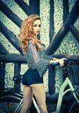 Den härliga flickan som bär den ultramarine blusen, och svarta sexiga kortslutningar parkerar in med cykeln Nätt röd hårkvinna so Royaltyfria Bilder