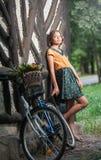 Den härliga flickan som bär en trevlig klänning med högskolablicken som har gyckel parkerar in, med cykeln som bär en härlig korg Royaltyfria Foton