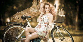 Den härliga flickan som bär en trevlig kort klänning som har gyckel parkerar in, med cykeln Nätt lång hårkvinna med romantiskt vi Royaltyfri Foto