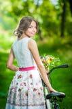 Den härliga flickan som bär en trevlig vit klänning som har gyckel parkerar in, med cykeln Sunt utomhus- livsstilbegrepp Nätt blo Royaltyfri Foto