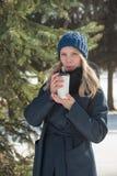 Den härliga flickan som går i vinterstad, parkerar med en påse och en drink royaltyfri bild