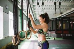 Den härliga flickan som gör en övning på idrottshallen, ringer i idrottshallen lyckligt le Royaltyfri Foto