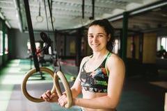 Den härliga flickan som gör en övning på idrottshallen, ringer i idrottshallen lyckligt le Royaltyfria Foton