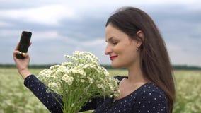 Den härliga flickan som gör selfie, foto med kamomill, blommar utanför stock video