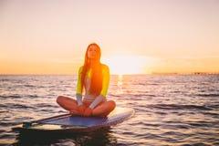 Den härliga flickan som kopplar av på, står upp skovelbrädet, på ett tyst hav med varma solnedgångfärger Fotografering för Bildbyråer