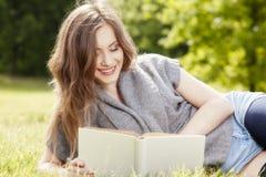 Den härliga flickan som läser en bok och, kopplar av Arkivfoton