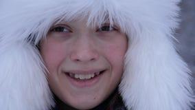Den härliga flickan som ler i den snöig vintern, parkerar Lycklig tonåring i snöig skog arkivfilmer