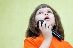Den härliga flickan som rymmer en mikrofon, sjunger och ser uppåt royaltyfria bilder