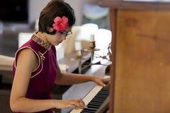 Den härliga flickan spelar det antika pianot Arkivbilder