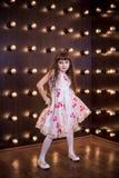 Den härliga flickan står i en ovanlig inre Arkivfoto