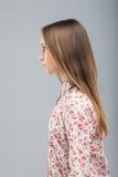 Den härliga flickan står i profil i studio Royaltyfri Fotografi