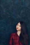 Den härliga flickan står nära väggen Royaltyfri Fotografi