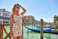 Den härliga flickan står vid floden i Venedig nära gondolen, Italien royaltyfria foton