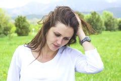 Den härliga flickan tänker om något hänsynsfullt med hennes hand på huvudet Arkivfoto