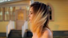 Den härliga flickan talar leenden och justerar hår nära trähus under fotoperiod i antikt gods lager videofilmer