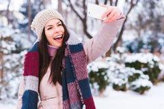 Den härliga flickan tar en självstående på en kall vinterdag Royaltyfri Foto