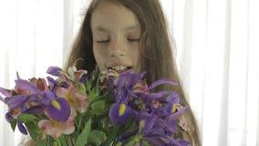 Den härliga flickan tycker om buketten av iriers och alstroemeria arkivfilmer