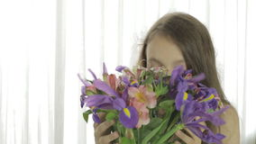 Den härliga flickan tycker om den skänkte buketten av blommor stock video