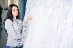 Den härliga flickan väljer hennes bröllopsklänning Stående i brud- sa Royaltyfri Bild