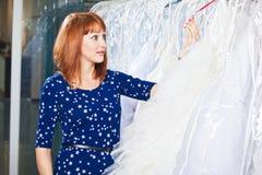 Den härliga flickan väljer hennes bröllopsklänning Stående i brud- sa Arkivbild