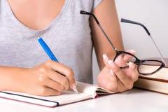 Den härliga flickastudenten skriver i anteckningsbok med pennan och hållande exponeringsglas royaltyfria foton