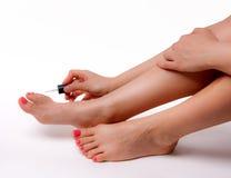 Den härliga foten med den perfekta brunnsorten spikar pedikyr på vit bakgrund Arkivbild