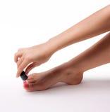 Den härliga foten med den perfekta brunnsorten spikar pedikyr på vit bakgrund Royaltyfri Fotografi