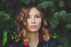 Den härliga framsidan av en le ung kvinna mot en bakgrund av gran förgrena sig Arkivfoto