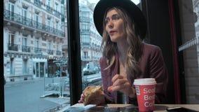 Den härliga fransyskan i en hatt äter en giffel i en coffee shop på bakgrunden av en fransk gata På tabellen är arkivfilmer