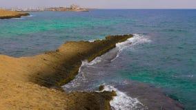 Den härliga fridsamma kusten med vaggar, vågor och horisonten stock video