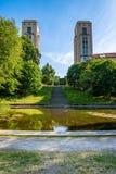 Den härliga fridsamma staden parkerar med ett damm, träd och tornbyggnader Fotografering för Bildbyråer