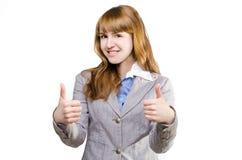 Den härliga gladlynta affärskvinnan visar upp tummen Fotografering för Bildbyråer