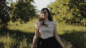 Den härliga gladlynta lyckliga unga flickan som bär den svarta kjolen med krabbt hår, går i banan i skog sprider hår och lager videofilmer