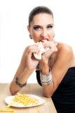 Den härliga glamourkvinnan äter snabbmat Fotografering för Bildbyråer