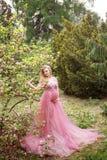 Den härliga gravida flickan i buk för hand för lång rosa fattiniklänning rörande och blickar på den blommande magnolian parkerar  Royaltyfria Bilder