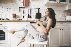 Den härliga gravida kvinnan i kök med koppen av mjölkar royaltyfri fotografi
