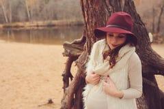Den härliga gravida kvinnan i modehatt på hemtrevligt varmt utomhus- går Arkivfoto